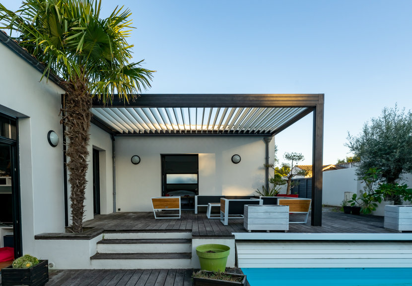 Trendy outdoor patio pergola. garden lounge, chairs, metal grill surrounded by landscaping